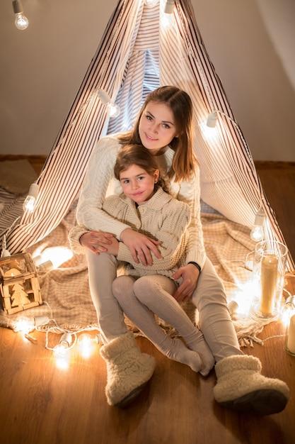 Schöne mutter und tochter heiligabend sitzen im gemütlichen innenraum Premium Fotos