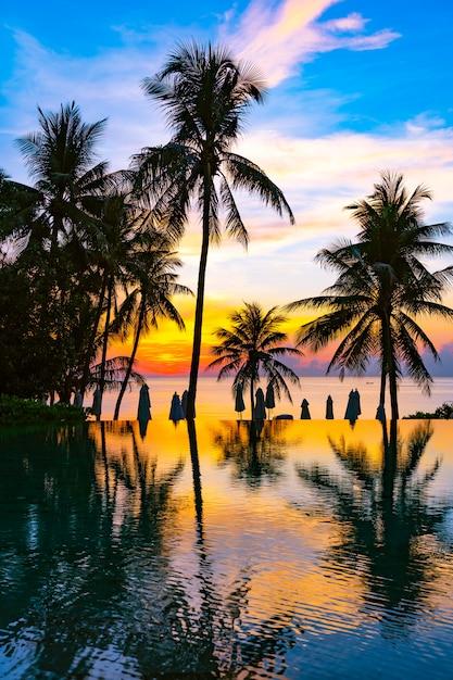Schöne naturlandschaft im freien mit seeozean- und kokosnusspalme um swimmingpool bei sunrsie oder sonnenuntergang Kostenlose Fotos