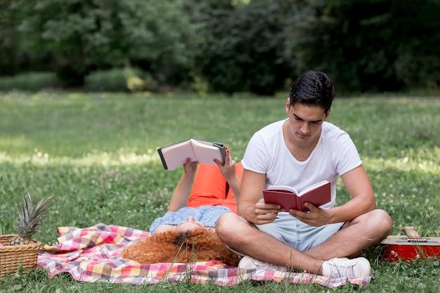 Schöne paare, die bücher lesen und picknicken Kostenlose Fotos