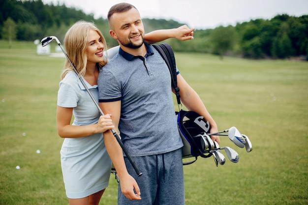 Schöne paare, die golf auf einem golfplatz spielen Kostenlose Fotos