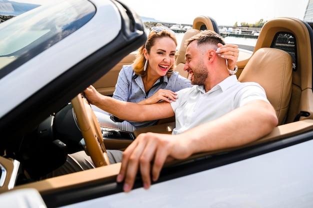 Schöne paare, die im auto lachen Kostenlose Fotos