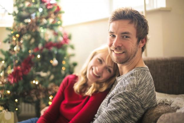 Schöne paare, die sich zu hause, sitzend vor dem weihnachtsbaum entspannen Premium Fotos
