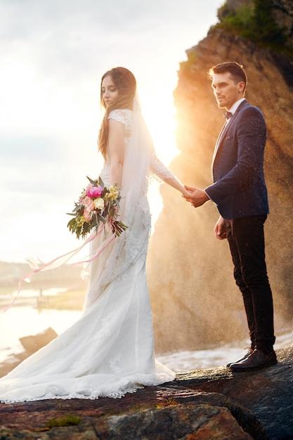 Schöne paare in der liebe, die auf felsen durch meer küsst Premium Fotos