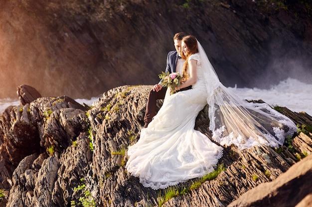 Schöne paare in der liebe, die das sitzen auf felsen küsst Premium Fotos