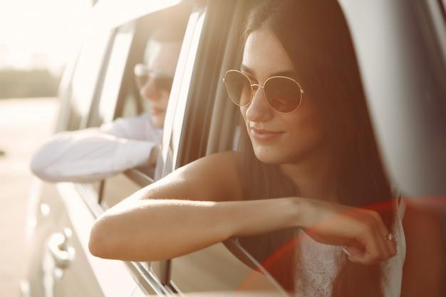 Schöne paare verbringen zeit in einem sommerpark, der in einem auto sitzt Kostenlose Fotos