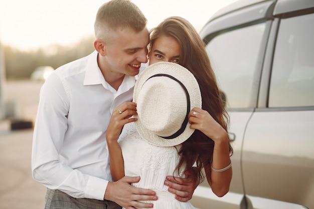 Schöne paare verbringen zeit in einem sommerpark nahe einem auto Kostenlose Fotos