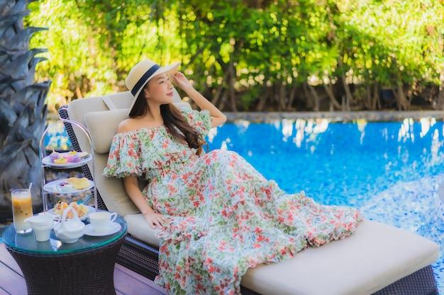Schöne porträt junge asiatische frau mit nachmittagstee gesetzt mit kaffee sitzen auf stuhl um schwimmbad Kostenlose Fotos
