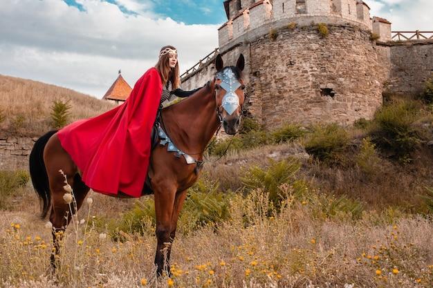 Schöne prinzessin mit dem roten kap, das ein pferd vor dem hintergrund eines turms und einer steinmauer reitet Premium Fotos