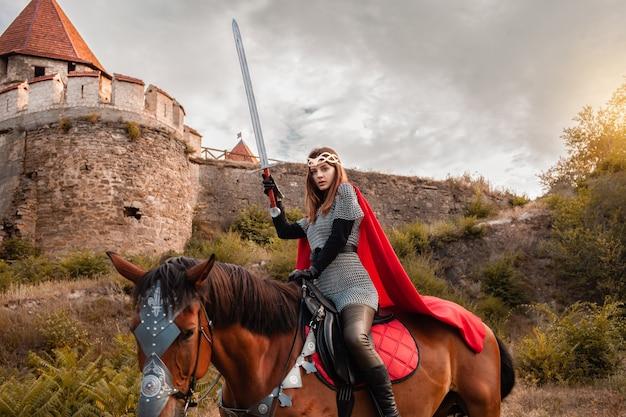 Schöne prinzessin mit rotem kap und mit einem schwert reiten ein pferd vor dem hintergrund eines turms und Premium Fotos