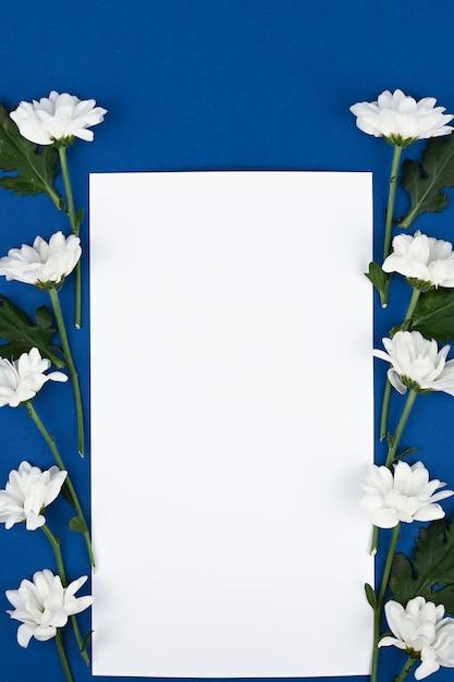 Schöne rechteckige blumenanordnung der weißen blumen mit einem leeren papierblatt Premium Fotos