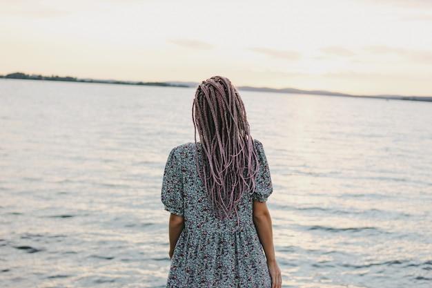 Schöne romantische junge frau mit afrikanischen zöpfen im kleid auf dem strand Premium Fotos