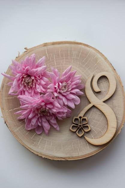 Schöne rosa blumen auf holzscheibe mit nummer acht für 8. märz, internationaler frauentag Premium Fotos