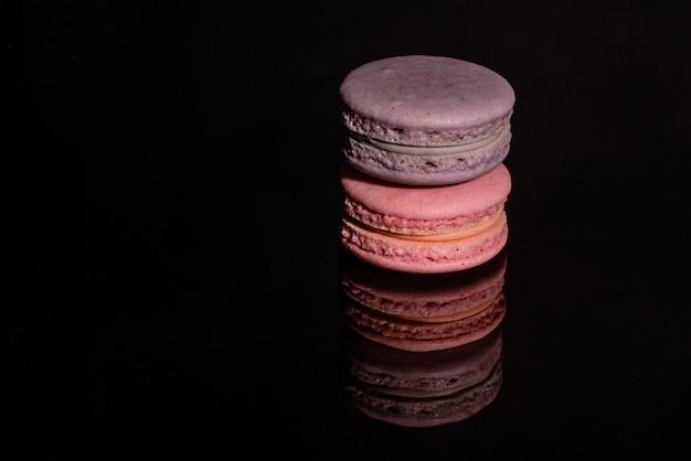 Schöne rosa geschmackvolle makronen auf einem dunklen hintergrund Premium Fotos