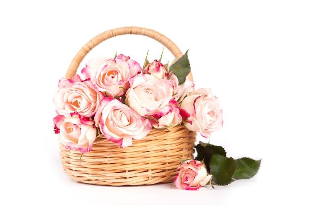Schöne rosa rosen in einem weidenkorb auf einem weißen hintergrund. Premium Fotos