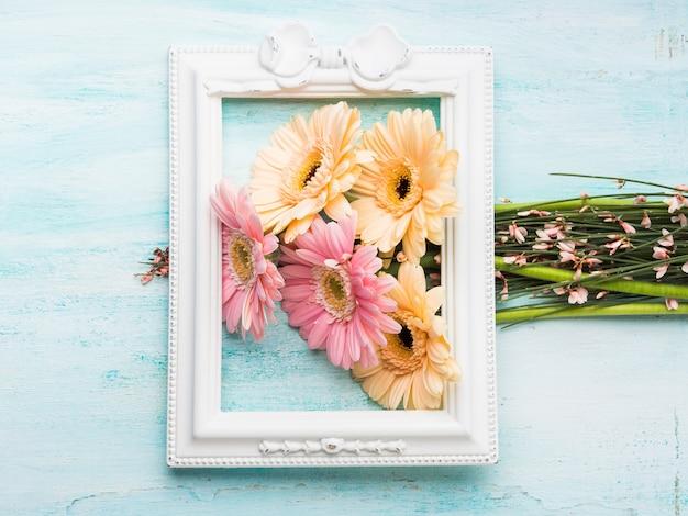 Schöne rosa und gelbe blumen im weißen rahmen auf grünem pastellhintergrund. frau, muttertagesgrußkarte. Premium Fotos