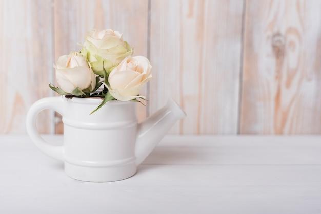 Schöne rosen in der keramischen kleinen gießkanne auf holztisch Kostenlose Fotos