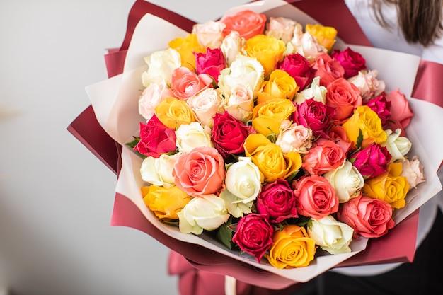 Schöne rosen in händen. frühling, sommer, blumen, farbkonzept. blumenlieferdienst Premium Fotos