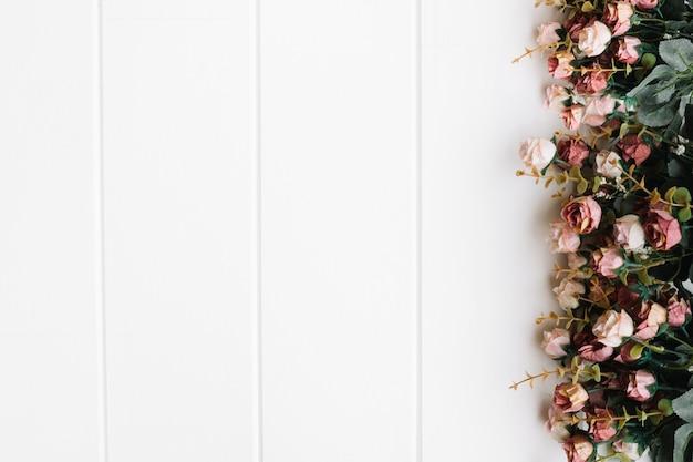 Schöne rosen über großen weißen hölzernen hintergrund mit platz auf der rechten seite Kostenlose Fotos