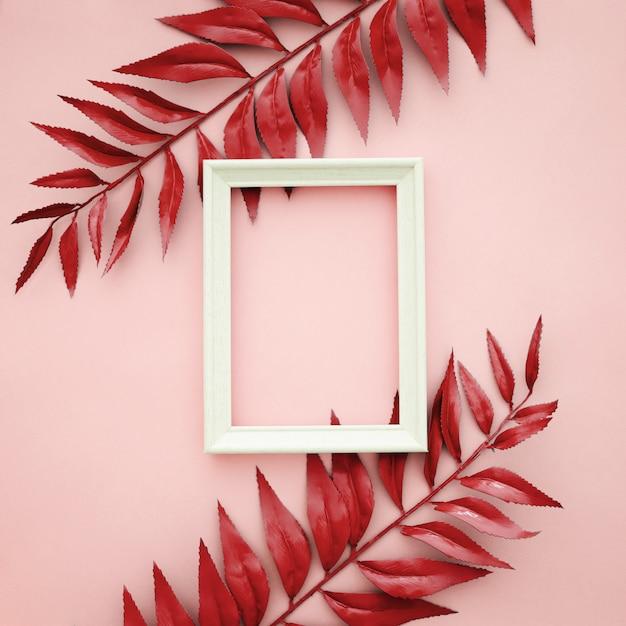 Schöne rote grenze verlässt auf rosa hintergrund mit leerem rahmen Kostenlose Fotos