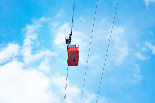 Schöne rote luftzugbahnkabine der weinlese, die über, lokalisiert auf hellblauem himmel bewegt Kostenlose Fotos