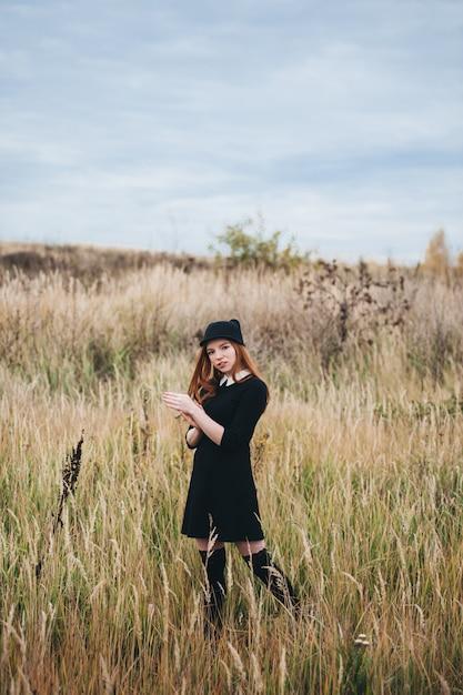Schöne rothaarige frau in einem schwarzen kleid geht auf ein herbstfeld. Premium Fotos