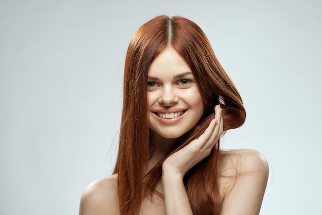 Schöne rothaarige frau mit nackten schultern und hellem hintergrund des langen haarglamours. Premium Fotos