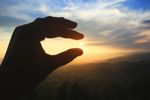 Schöne schattenbildhand, die an sonne und sonnenuntergang auf dem berg hält. macht und hoffnung konzept. Premium Fotos