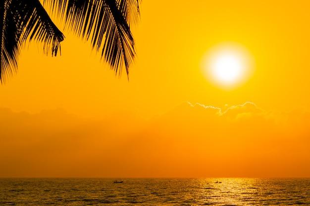 Schöne schattenbildkokosnusspalme auf himmel neary seeozeanstrand zur sonnenuntergang- oder sonnenaufgangzeit Kostenlose Fotos