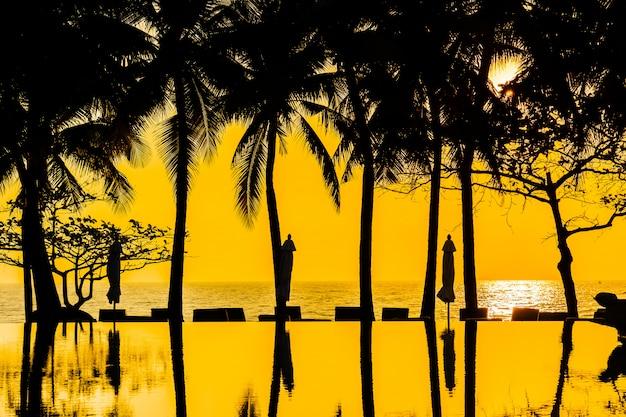 Schöne schattenbildkokosnusspalme auf himmel um swimmingpool im neary seeozean b Kostenlose Fotos