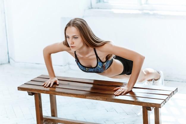 Schöne schlanke brünette, die einige liegestütze im fitnessstudio macht Kostenlose Fotos