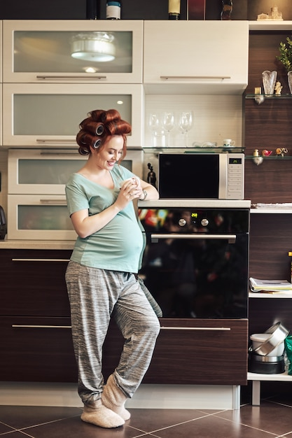 Schöne schwangere frau, die zu hause mit einer tasse tee entspannt Premium Fotos