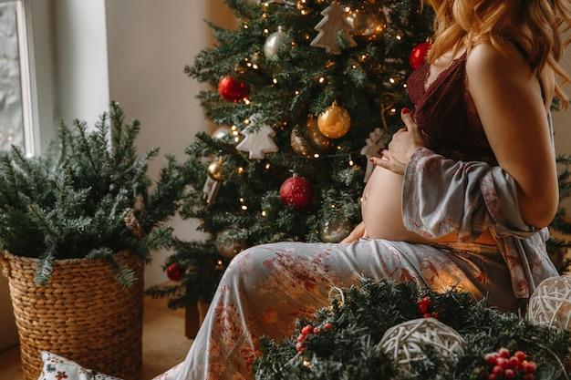 Schöne schwangere frau in der bequemen kleidung, die auf einer tabelle nahe dem weihnachtsbaum sitzt. Premium Fotos