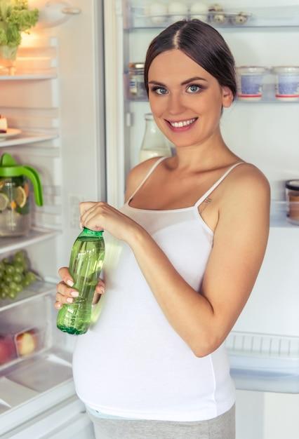 Schöne schwangere frau ist eine flasche getränk. Premium Fotos