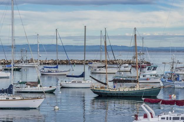 Schöne segelboote auf dem wasser nahe altem fischmannkai, der in monterey, ca, usa gefangen genommen wird Kostenlose Fotos