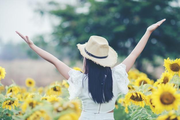 Schöne sexy frau in einem weißen kleid zu fuß auf einem feld von sonnenblumen Kostenlose Fotos