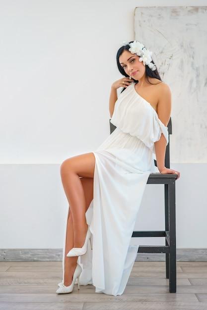 Schöne sexy junge frau im weißen kleid, das die aufstellung auf stuhl sitzt. Premium Fotos