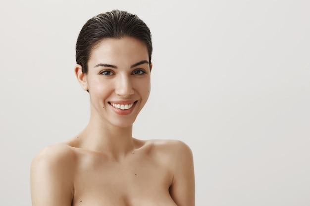 Schöne sinnliche brünette, die nackt steht und sorglos