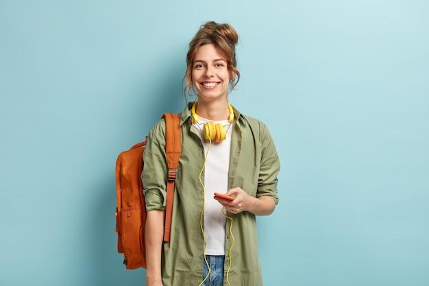 Schöne smilig weibliche reisende hat freizeit, genießt online-kommunikation, verbunden mit kopfhörern, hört musik von der wiedergabeliste, trägt lässiges weißes t-shirt und grünes hemd, trägt rucksack Kostenlose Fotos