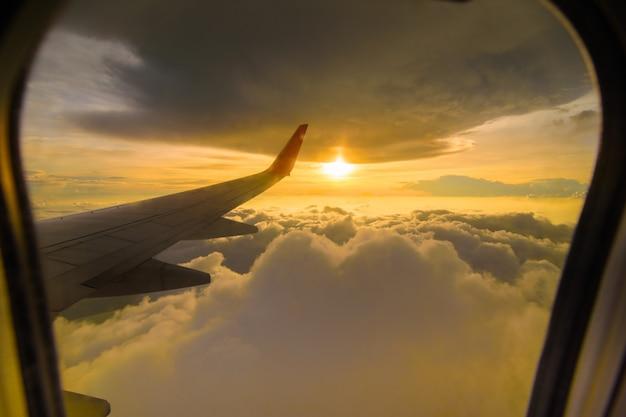 Schöne sonnenunterganghimmelwolken, die durch das flugzeugfenster sehen. Premium Fotos