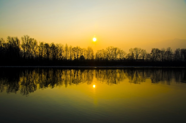 Schöne sonnenuntergangslandschaft über dem see mit den im wasser reflektierten silhouetten von bäumen Kostenlose Fotos