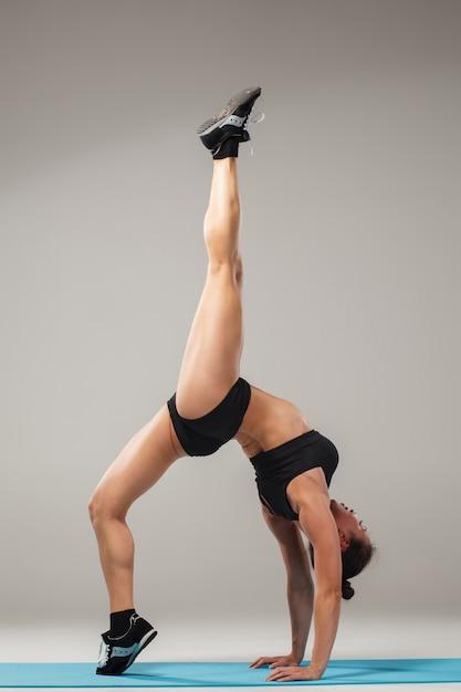 Schöne sportliche frau, die in der akrobatenhaltung steht Kostenlose Fotos