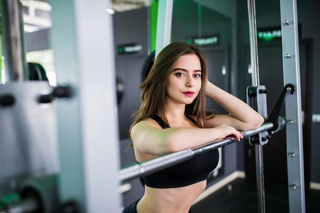 Schöne stark lächelnde dame mit langhantel posiert im sportclub Kostenlose Fotos