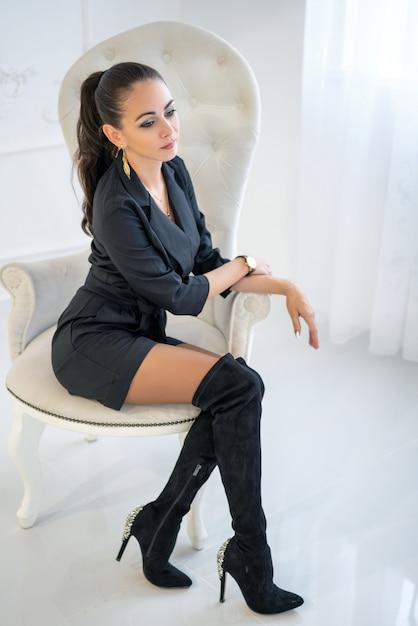 Schöne stilvolle überzeugte frau, die in einem weißen stuhl im studio sitzt Premium Fotos