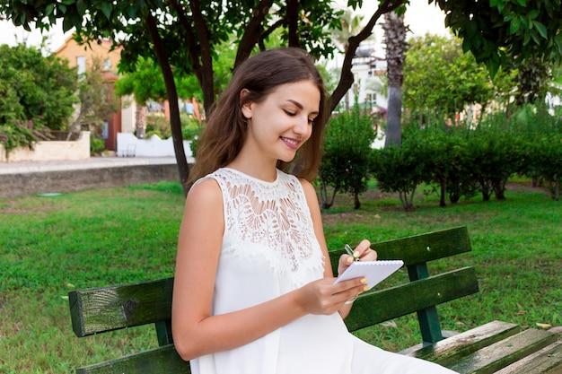 Schöne studentin schreibt ihre ideen und gedanken in das notizbuch, das auf der bank im park sitzt Premium Fotos