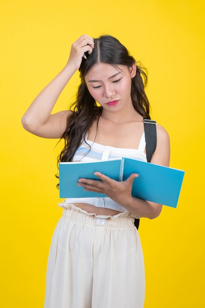 Schöne studentinnen halten notizbücher und stifte Kostenlose Fotos