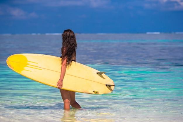 Schöne surferfrau, die während der sommerferien surft Premium Fotos