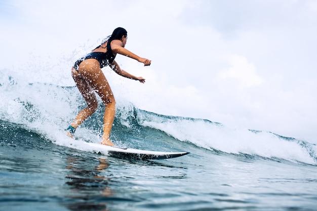 Schöne surferin auf einem brett reiten Kostenlose Fotos