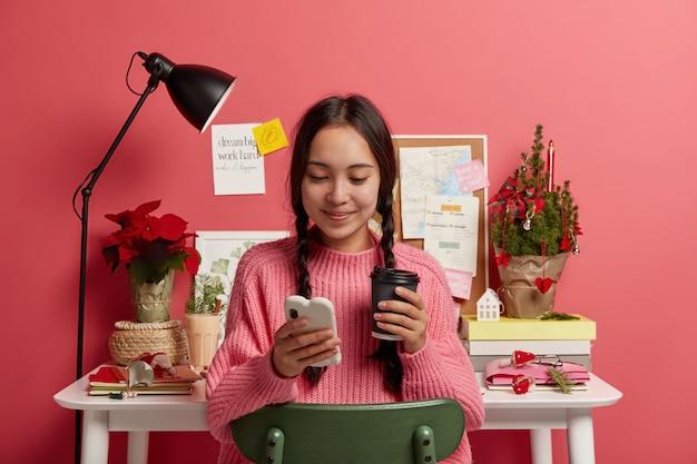 Schöne teenager-mädchen mit zwei zöpfen hält handy, hält einweg tasse getränk Kostenlose Fotos
