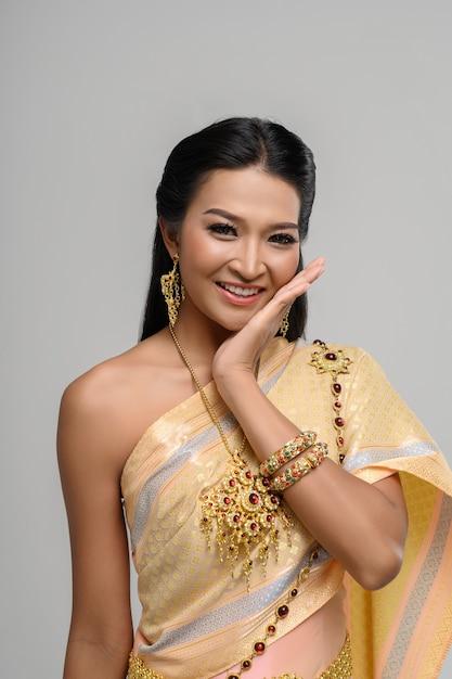 Schöne thailändische frau, die ein thailändisches kleid
