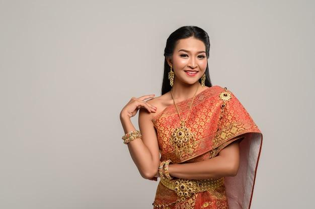Schöne thailändische frau, die ein thailändisches kleid und ein glückliches lächeln trägt. Kostenlose Fotos